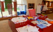 Display of embroidered tablecloths, dresses and cushions